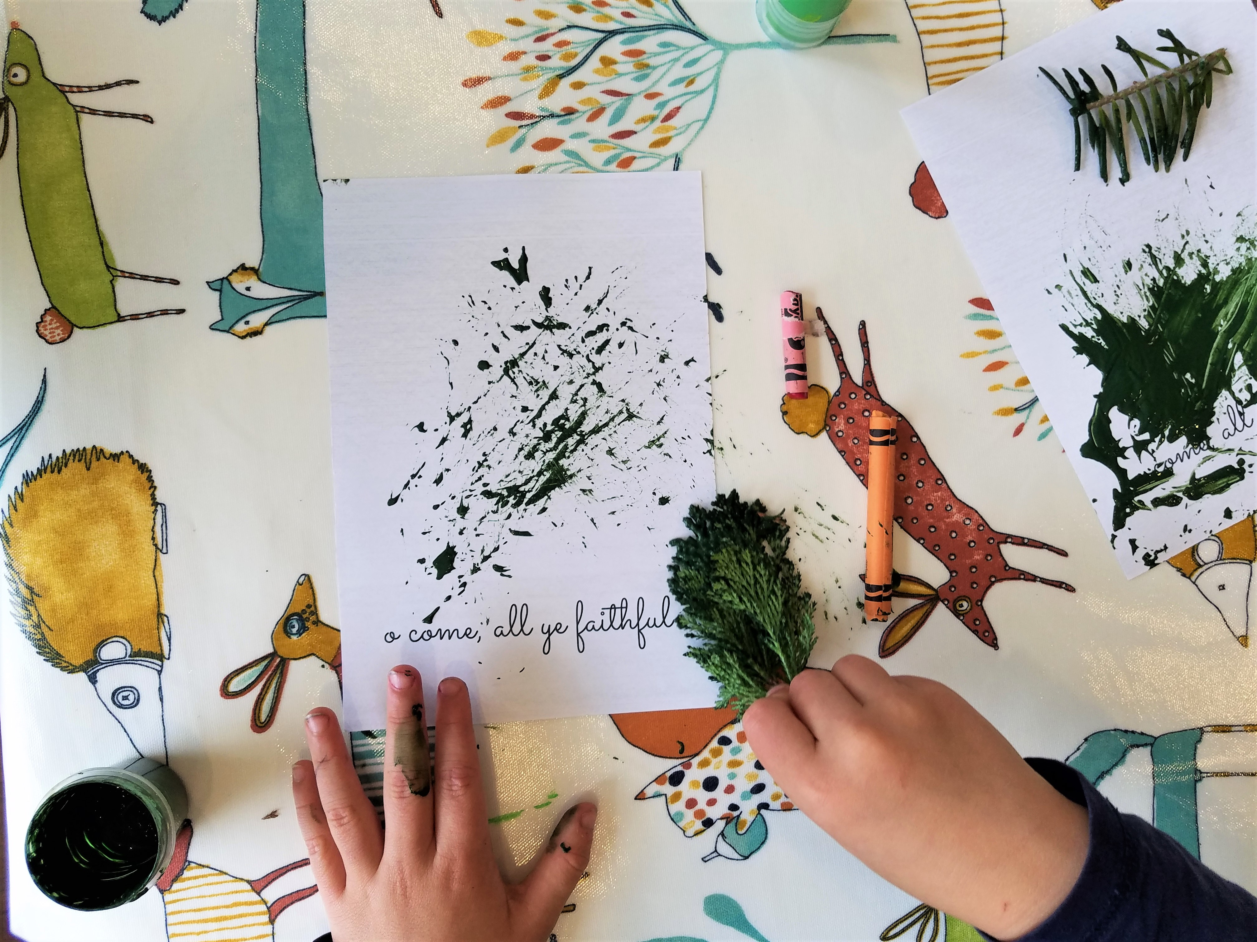 child using nature items to make Christmas cards